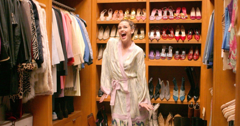 Mujer alegre en bata y con un closet lleno de zapatos atrás