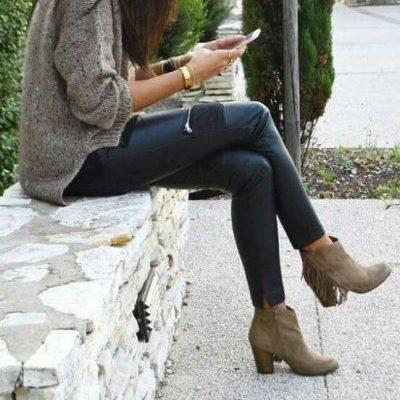 Mujer sentada escribe en su celular y tiene puestos unos botines color marrón con flecos