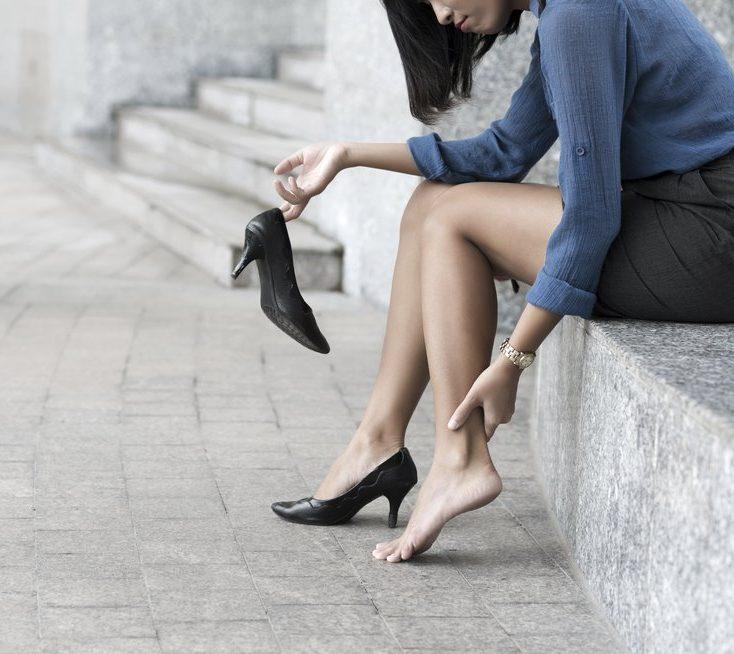 Mujer se saca un zapato de taco en la calle con cara de estar adolorida
