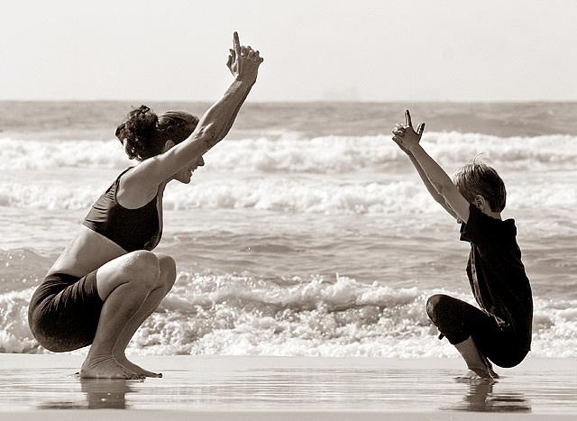 Madre e hijo practicando yoga en la playa