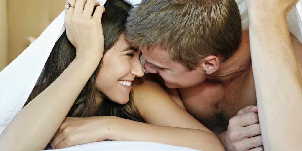 Caucasian couple kissing under sheet