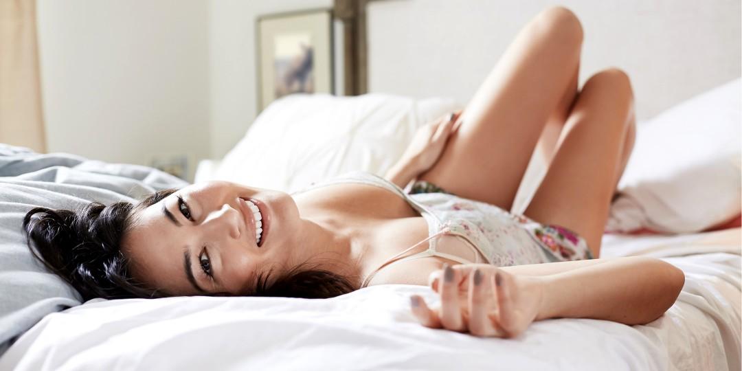 Mujer feliz, acostada en una cama