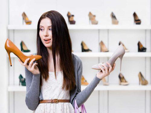 Mujer mira indecisa entre dos pares de zapatos