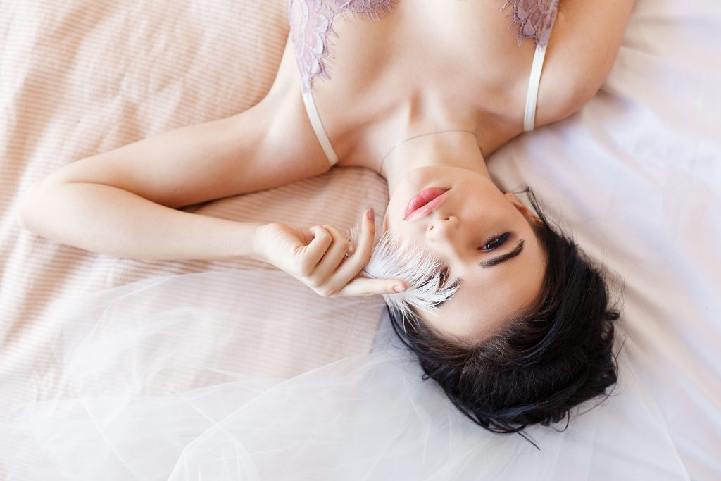 Sensual Brunette Beautiful Woman Lying On Bed In White Lingerie Covering Eye With Feather