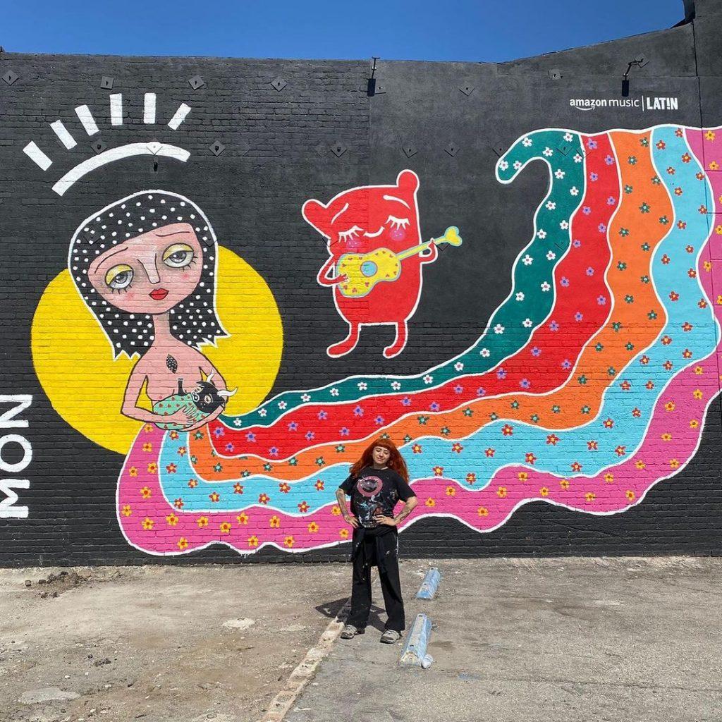 Mon Laferte junto al mural que realizó