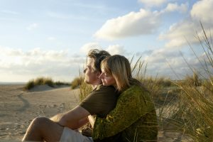 Couple Sitting Embracing On Beach